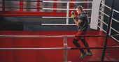 Training His Boxing Skills. Muscular Tattooed Boxer In Sports Clothing Punching On Red Boxing Ring W poster
