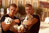 Always Carrying About Each Other. Twins Men Hold Pedigree Dogs. Spitz Dogs Love The Company Of Their poster