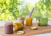 baby food, healthy eating and nutrition concept - vegetable or fruit puree in glass jars and feeding poster