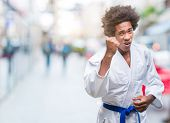 Afro american man wearing karate kimono over isolated background angry and mad raising fist frustrat poster