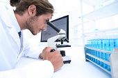 Young laboratory scientist looking at microscope in laboratory poster