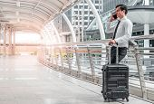 Young Business Man Man On Business Trip Standing With His Luggage And Making A Call Outside Airport. poster