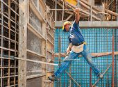 stock photo of scaffolding  - Authentic construction worker in a difficult balancing position between scaffold and formwork frame - JPG