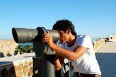 stock photo of ceuta  - Beautiful guy looking through telescope - JPG