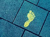 stock photo of painted toes  - Yellow paint footprint on bluish sidewalk symbolize individuality - JPG