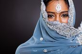 young indian woman in sari with her face covered on black background