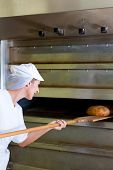 Female baker baking fresh bread in the bakehouse