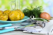 Boiled potatoes on platen on wooden board near napkin on wooden table on nature background