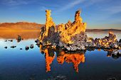 Orange sunset on Mono Lake. Outliers - bizarre calcareous tufa formation reflected in the smooth water.