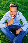 Happy handsome middle-aged man eating ice- cream outdoors
