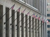 Ten American Flags on poles on a building