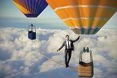 foto of dizziness  - Equilibrist businessman over a hot air balloon - JPG