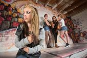 stock photo of humiliation  - Insecure European teenager being bullied by female gang - JPG