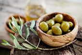 stock photo of vegan  - Fresh olives and olive oil on rustic wooden background - JPG