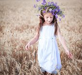 little girl with a wreath on his head in a field of wheat