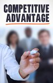 Businessman underlining the word competitive advantage in front of a business team