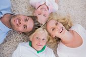 Overhead of family lying on the carpet at home