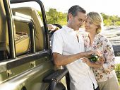 Happy adult couple by jeep with man pouring wine in glass