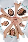 Smiling group of volunteers piling up their hands on white background