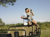 Young couple on Safari stehen in Jeep und looking through binoculars