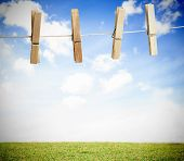 Clothespin on a laundry line outside with bright blue sky with green landscape