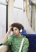 Young teenage boy listening music with headphones in commuter train