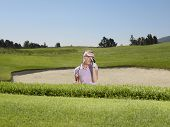 Young disappointed female golfer in sand trap