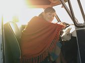 picture of campervan  - Portrait of happy young woman wrapped in shawl sitting at driver - JPG