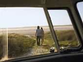 stock photo of campervan  - Full length of loving young couple walking towards beach view from campervan window - JPG