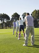 Rear view of young golfers standing in row teeing off on golf course