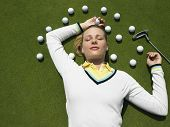Beautiful female golfer lying on putting green with golf balls and club