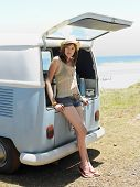 Full length of young woman leaning on open tailgate of van at beach