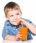 Little boy is drinking carrot juice using straw, isolated over white