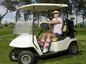 Beautiful female golfer driving golf cart in course