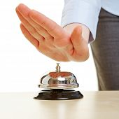 Hand on a hotel bell on a reception