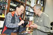 Assistant seller help buyer by demonstrating digital photo camera at shop store