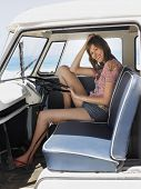 stock photo of campervan  - Full length portrait of happy young woman sitting in driver - JPG