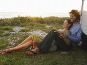 stock photo of campervan  - Full length of young couple on beach leaning on campervan - JPG