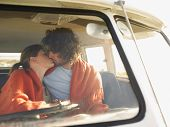 Loving young couple kissing in campervan during roadtrip