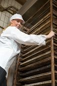 Baker Pushing Rack Full Of Bread Into The Oven