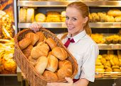 Baker In Bakery With Basket Full Of Bread