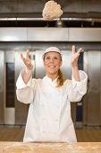 Baker Throwing Dough Into Air In Bakehouse