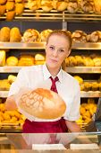 Shopkeeper In Bakery Giving Bread To Customer