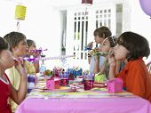 Side view of six children at outdoor table blowing party puffers