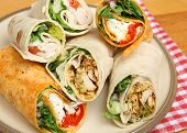Plate of wrap sandwiches filled with chicken and cheese.