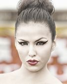 Beautiful woman pursing red lips with cat eye style liner and hair in bun.
