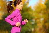 picture of ponytail  - Woman running in autumn fall forest - JPG