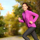 Young Asian woman running female jogger happy. Female runner jogging in park in autumn park forest i