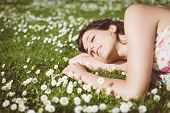 stock photo of rest-in-peace  - Happy woman resting and day dreaming lying down on grass and daisies in park outdoors - JPG