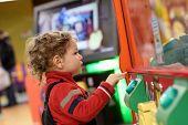 Child Playing On Game Machine